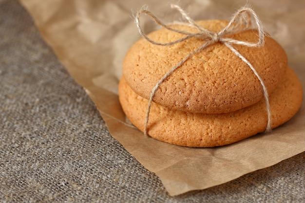 Biscoitos de aveia dois pedaços amarrados com uma corda na toalha de mesa de estopa e papel kraft de embrulho.
