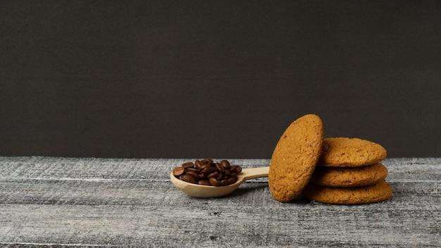 Biscoitos de aveia e colher de pau com grãos de café na mesa preta