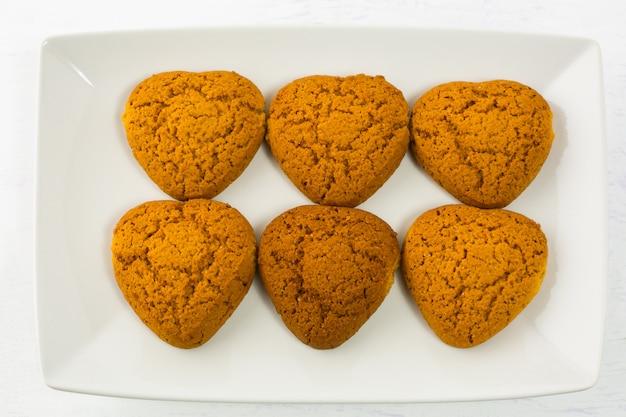 Biscoitos de aveia em forma de coração na chapa branca
