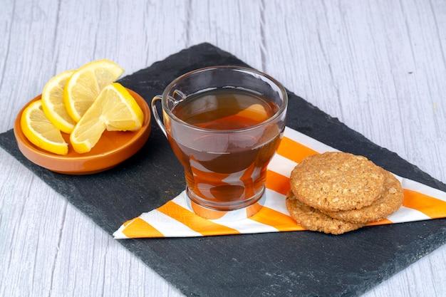 Biscoitos de aveia em guardanapo e prato de pedra retangular acompanhados por uma xícara de chá e um pires com rodelas de limão