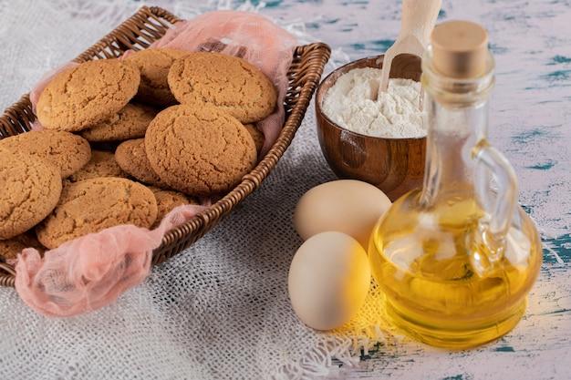 Biscoitos de aveia em uma bandeja de cesta de madeira com ingredientes ao redor.