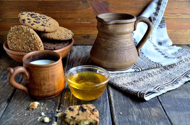 Biscoitos de aveia em uma placa de cerâmica, leite em uma caneca de cerâmica, jarro de barro, guardanapo em placas de madeira velhas.