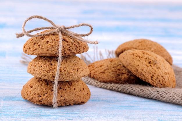Biscoitos de aveia empilhados em primeiro plano em uma mesa de madeira azul com um guardanapo. assar. gostoso.