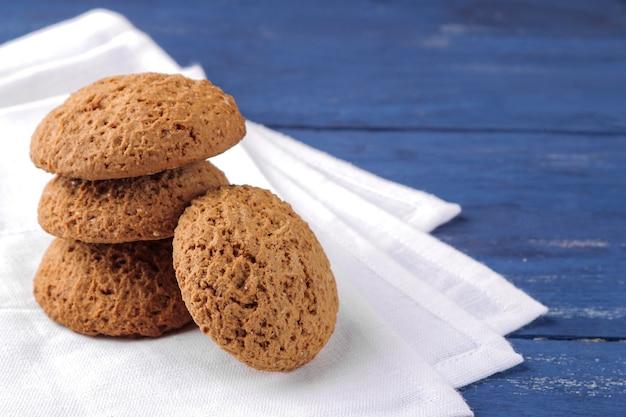 Biscoitos de aveia empilhados em um guardanapo branco sobre uma mesa de madeira azul. assar. gostoso.