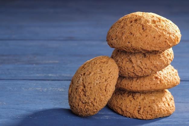Biscoitos de aveia empilhados em uma mesa de madeira azul. assar. plano saboroso