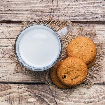 Biscoitos de aveia naturais e um copo de leite em um de madeira. estilo rústico.