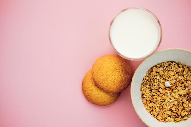 Biscoitos de aveia um copo de leite e mingau em um fundo rosa