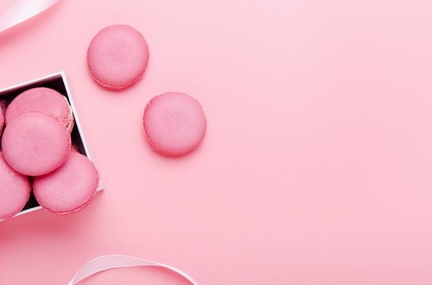 Biscoitos de biscoito rosa em um fundo rosa na caixa. o conceito de doces, bolos, junk food. composição mínima. copie o espaço, vista superior, configuração plana