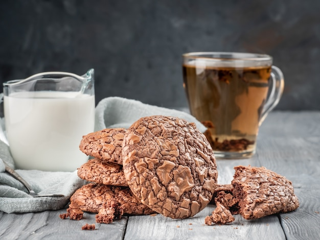 Biscoitos de brownie em uma mesa de madeira com chá e leite. copie o espaço.