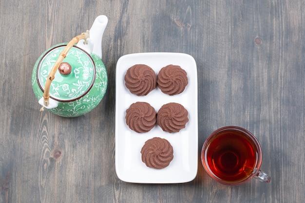 Biscoitos de cacau deliciosos em prato branco com chá quente