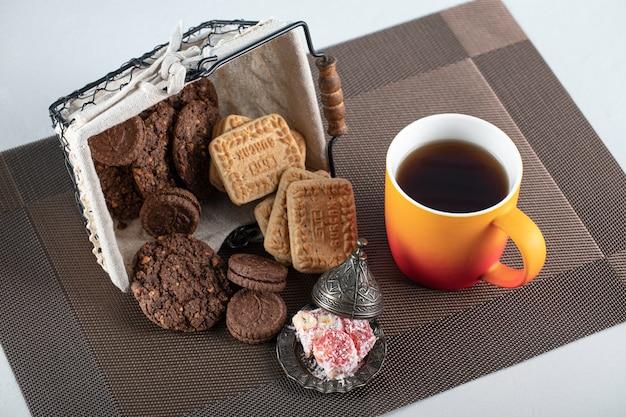 Biscoitos de cacau e manteiga em uma cesta com uma xícara de chá
