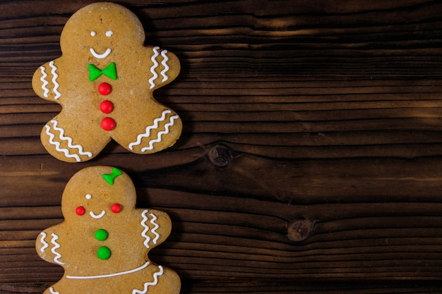 Biscoitos de casal de pão de mel de natal na mesa de madeira. vista do topo