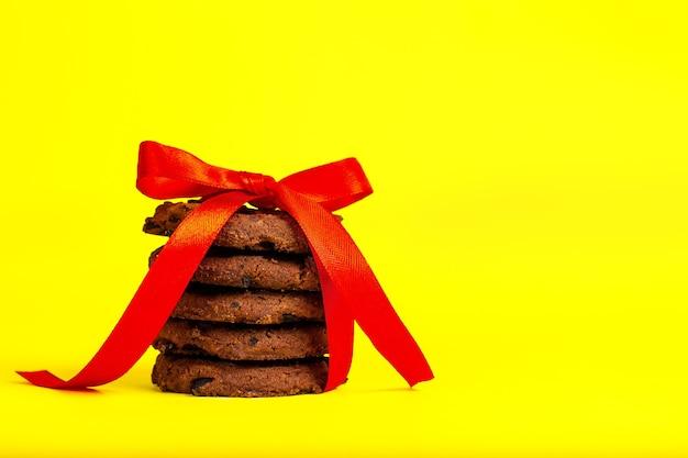 Biscoitos de chocolate amarrados com uma fita vermelha em um fundo amarelo.