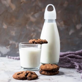 Biscoitos de chocolate ao lado de uma garrafa de vidro e um copo de leite sobre uma mesa cinza
