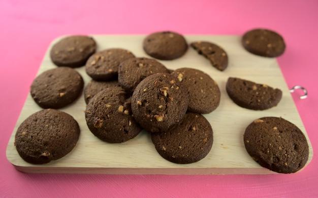 Biscoitos de chocolate assados escuros em uma tábua de madeira com fundo acrílico rosa