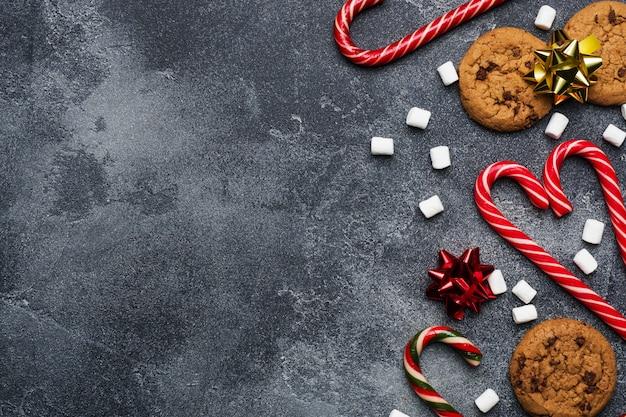 Biscoitos de chocolate bastões de natal caramelo cenário ouro vermelho e marshmallow em cinza escuro. quadro de copyspace.