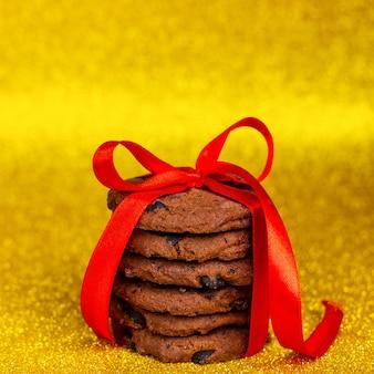Biscoitos de chocolate caseiros amarrados com uma fita vermelha de fundo amarelo brilhante