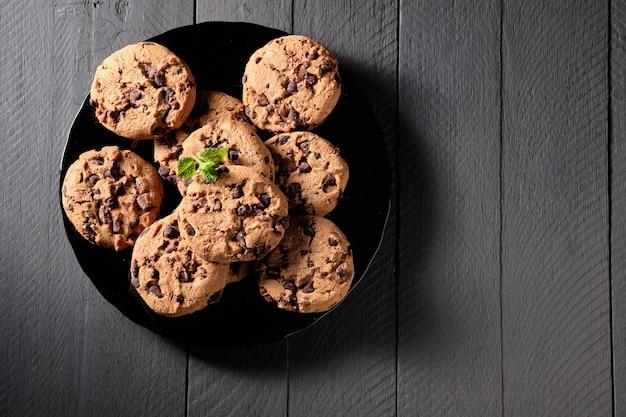 Biscoitos de chocolate caseiros com folhas de hortelã na mesa escura e rústica