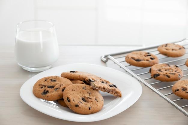Biscoitos de chocolate caseiros em chapa branca na prateleira de refrigeração com copo de leite na mesa de madeira.