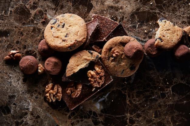 Biscoitos de chocolate caseiros frescos com bombons de chocolate na superfície de mármore escuro.
