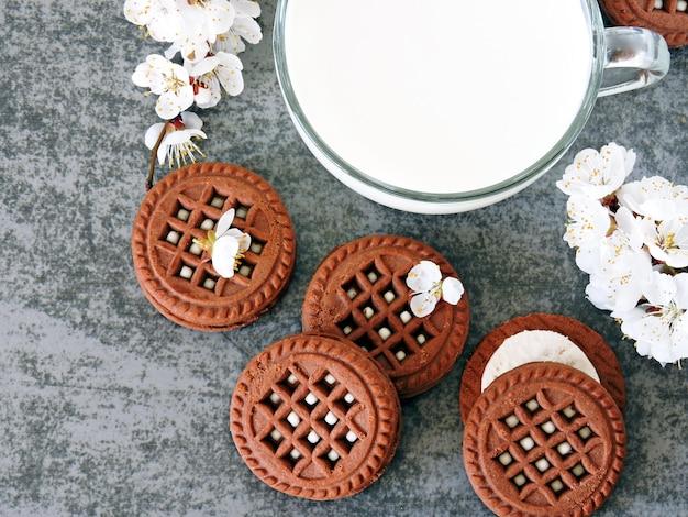 Biscoitos de chocolate com creme branco e flores de sakura