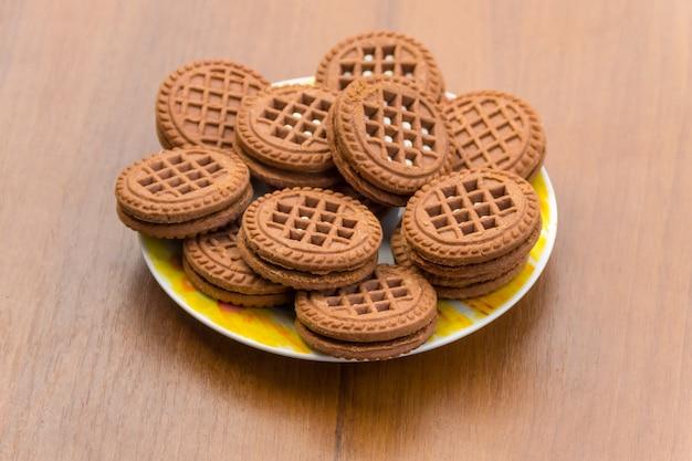 Biscoitos de chocolate com recheio de creme na mesa de madeira