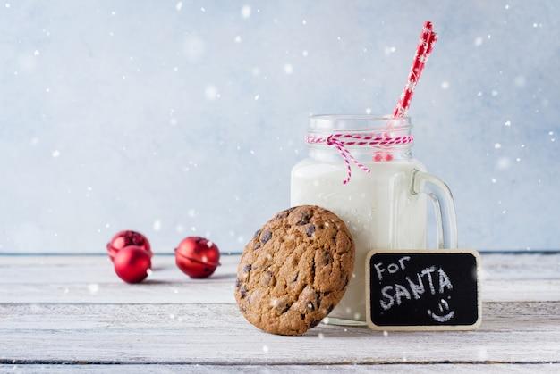 Biscoitos de chocolate com um copo de leite no guardanapo listrado azul sobre uma mesa branca