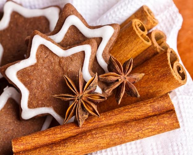 Biscoitos de chocolate de natal em forma de estrelas com açúcar de confeiteiro e canela