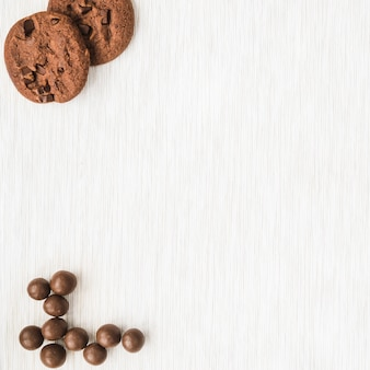 Biscoitos de chocolate e bola em fundo de textura de madeira