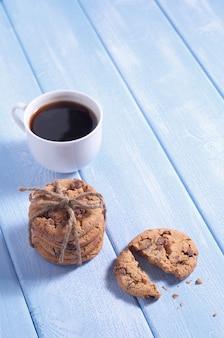 Biscoitos de chocolate e café no fundo azul de madeira