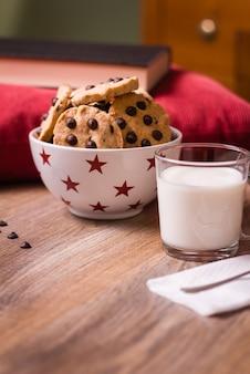 Biscoitos de chocolate e leite no fundo de madeira