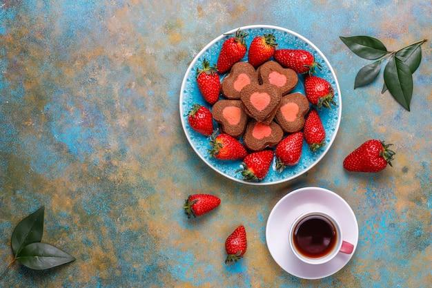 Biscoitos de chocolate e morango em forma de coração com morangos frescos, vista superior