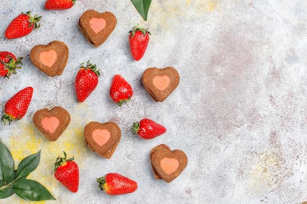 Biscoitos de chocolate e morango em forma de coração com morangos frescos