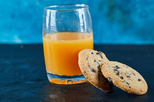 Biscoitos de chocolate e um copo de suco de laranja na mesa escura