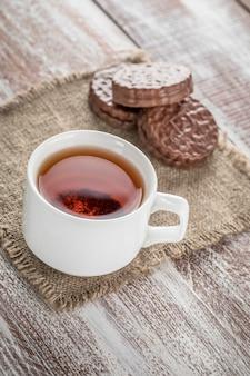 Biscoitos de chocolate e uma caneca de chá na mesa de madeira branca.