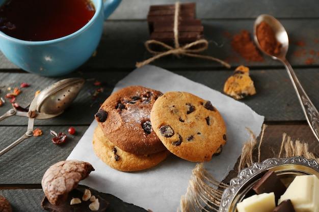 Biscoitos de chocolate e uma xícara de chá no fundo de madeira