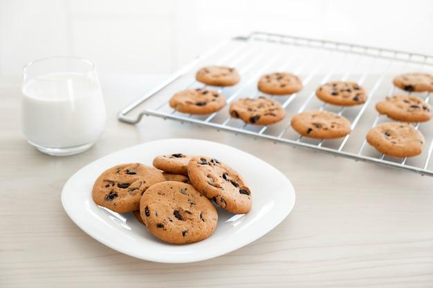 Biscoitos de chocolate em prato branco e bandeja com um copo de leite na mesa de madeira clara