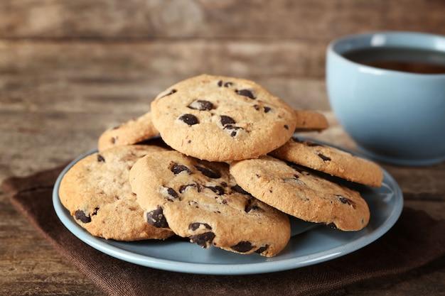 Biscoitos de chocolate em um prato azul e uma xícara de chá na mesa de madeira