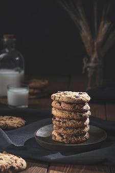 Biscoitos de chocolate empilhados, com um copo e uma garrafa de leite em uma base de madeira