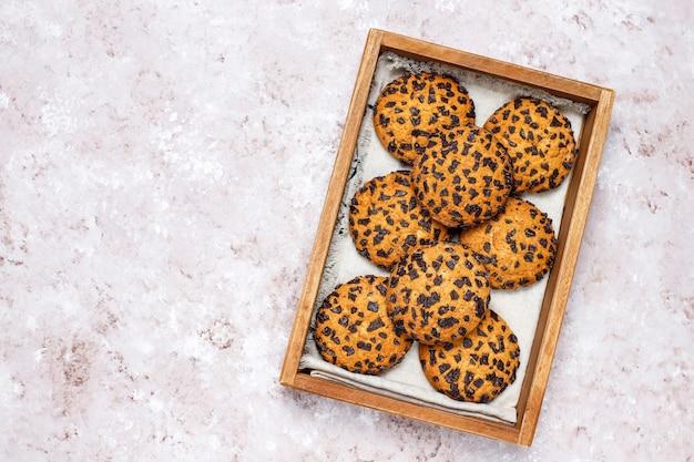 Biscoitos de chocolate estilo americano na bandeja de madeira sobre fundo claro de concreto.