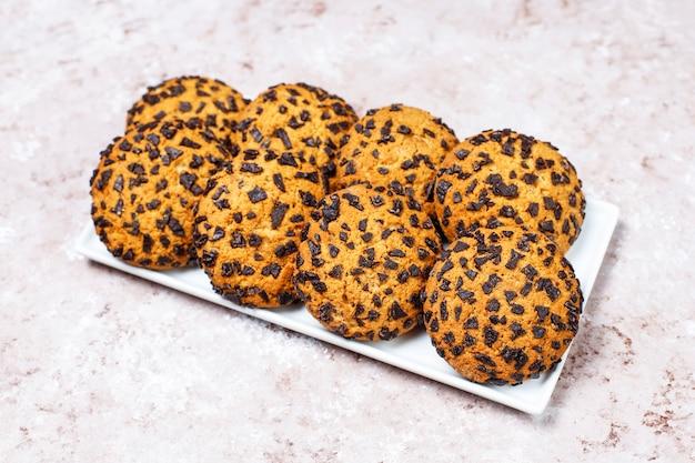 Biscoitos de chocolate estilo americano sobre fundo claro de concreto.