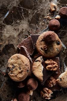Biscoitos de chocolate fresco com bombons de chocolate na superfície de mármore escuro.