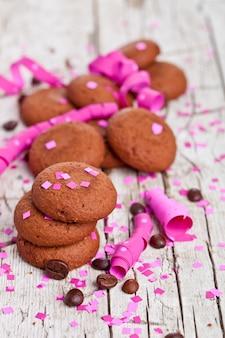 Biscoitos de chocolate frescos, grãos de café, fitas cor de rosa e confetes