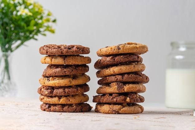 Biscoitos de chocolate. fundo com jarro de flores desfocado e leite.