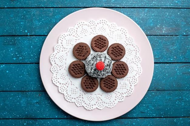 Biscoitos de chocolate gostosos com bolo de chocolate na mesa rústica e azul biscoito doce de chocolate