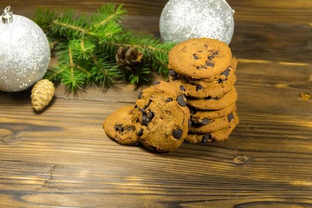 Biscoitos de chocolate na frente da decoração de natal na mesa de madeira