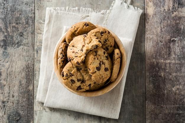 Biscoitos de chocolate na tigela de madeira na mesa de madeira, vista superior