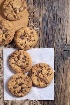 Biscoitos de chocolate na velha mesa de madeira, vista superior