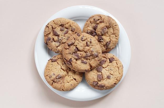 Biscoitos de chocolate no prato sobre fundo claro, vista superior