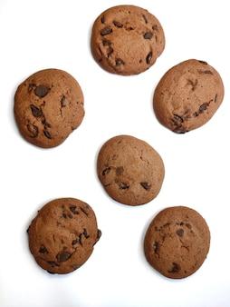 Biscoitos de chocolate redondos com pedaços de chocolate isolados encontram-se em um fundo branco